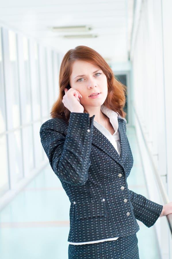 Schöne Geschäftsfrau, die mit Telefon spricht lizenzfreie stockfotos