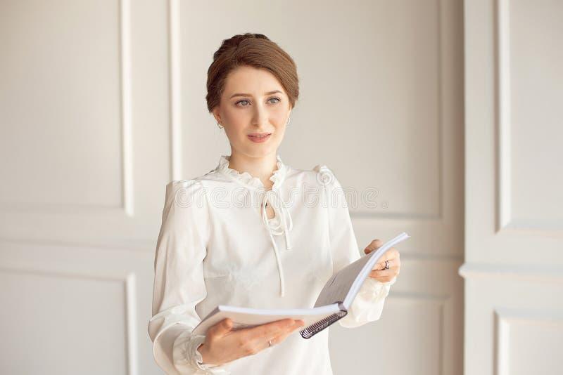 Schöne Geschäftsfrau in einem weißen Hemd und in dunklen Hosen, die einen Ordner mit Dokumenten halten lizenzfreie stockbilder