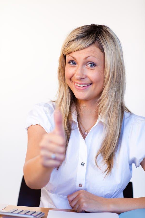 Schöne Geschäftsfrau mit den Daumen oben im Büro lizenzfreie stockbilder