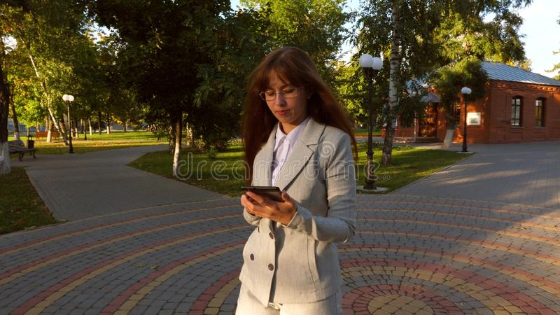 Schöne Geschäftsfrau mit Gläsern gehend entlang die Gasse im Park mit Tablette in ihren Händen, Mädchen in einem hellen Geschäft lizenzfreie stockbilder