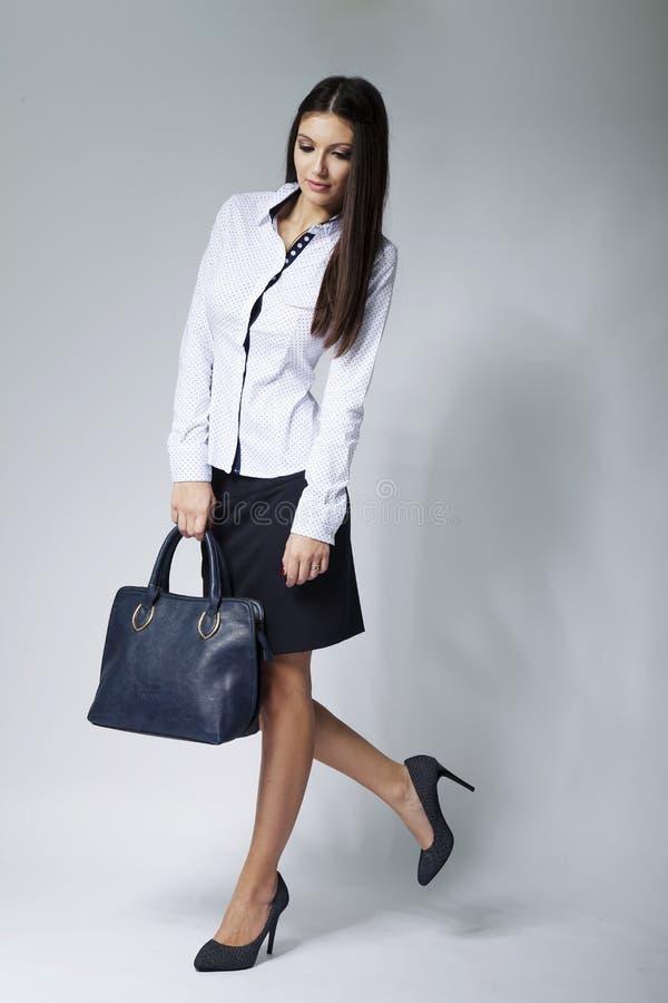 Schöne Geschäftsfrau mit Handtasche lizenzfreie stockfotografie