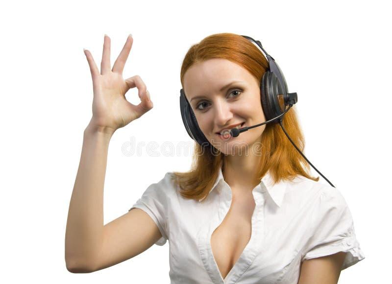 Schöne Geschäftsfrau mit Kopfhörer stellt O.K. dar lizenzfreies stockfoto