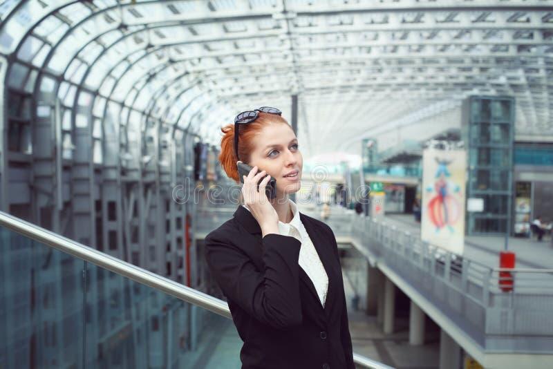Schöne Geschäftsfrau mit Zelle lizenzfreie stockbilder