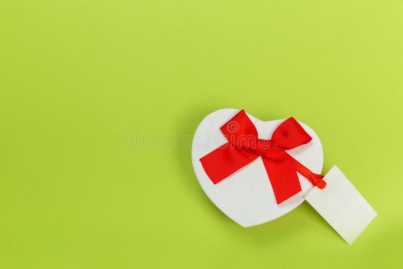 Schöne Geschenkboxen wickelten im Papier mit einem roten Band und in einem Bogen auf einer grünen Oberfläche ein Beschneidungspfa lizenzfreies stockbild