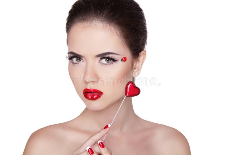 Schöne Gesichtsfrau mit dem hellen Make-up des Zaubers, das Herz hält. T stockbilder