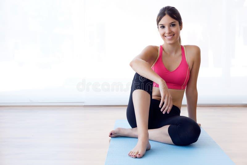 Schöne gesunde junge Frau, die zu Hause Übung tut stockfoto