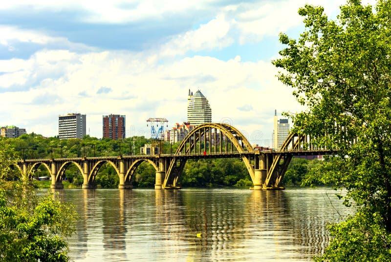Schöne gewölbte Merefoherson-Brücke auf dem Dnieper-Fluss und eine Ansicht der Dnipro-Stadtwolkenkratzer lizenzfreies stockbild