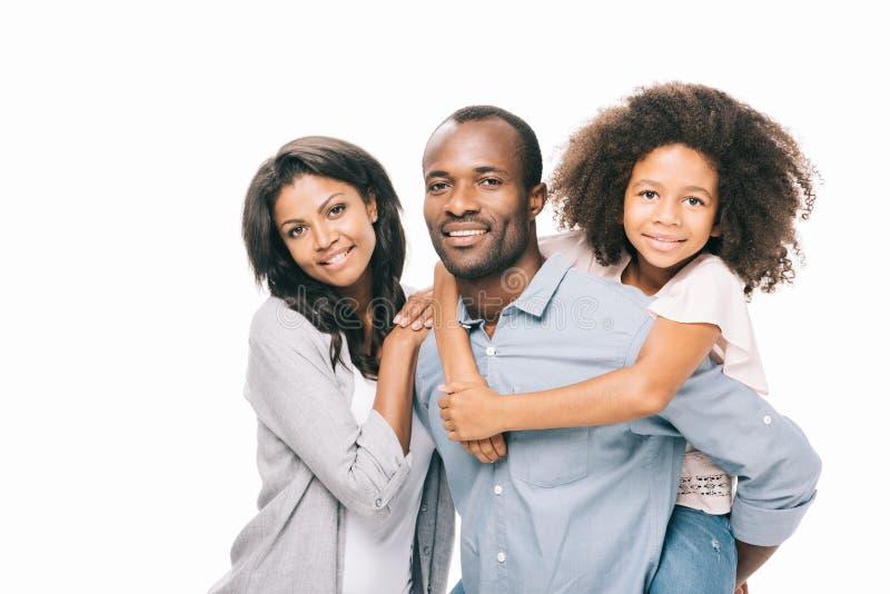 schöne glückliche Afroamerikanerfamilie mit einem Kind, das an der Kamera lächelt stockfotografie
