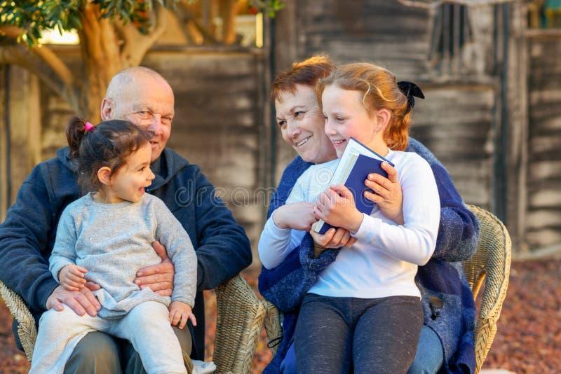 Schöne glückliche alte Paare und Enkelinnen, die zusammen ein Buch in der Natur bei Sonnenuntergang lesen stockbilder