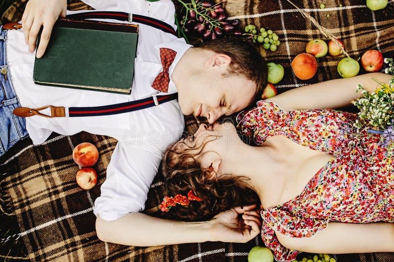 Schöne glückliche Braut und stilvoller Retro- Bräutigam, die auf Tweed bla liegt lizenzfreies stockfoto