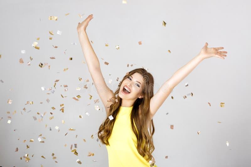 Schöne glückliche Brunettefrau mit dem langen Haarlächeln und -Konfettis fällt überall Party Zeit lizenzfreie stockfotos