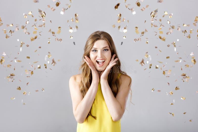 Schöne glückliche Brunettefrau mit dem langen Haarlächeln und -Konfettis fällt überall Party Zeit stockfotos