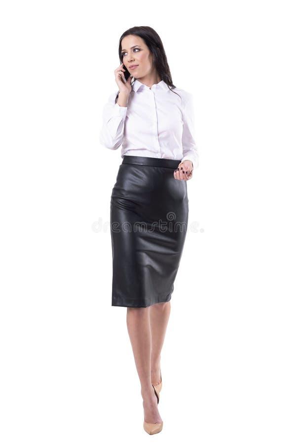 Schöne glückliche erfolgreiche überzeugte Geschäftsfrau, die am Handy geht und spricht lizenzfreies stockfoto