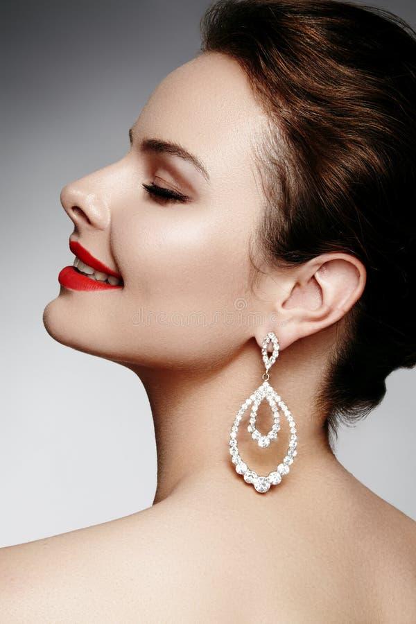 Schöne glückliche Frau in den Luxusmodeohrringen Glänzender Schmuck des Diamanten mit brilliants Sexy Retrostilporträt stockfoto