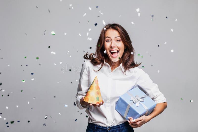 Schöne glückliche Frau an der Feierpartei mit den Konfettis, die überall auf sie fallen Des Geburtstages oder des Sylvesterabends lizenzfreies stockfoto