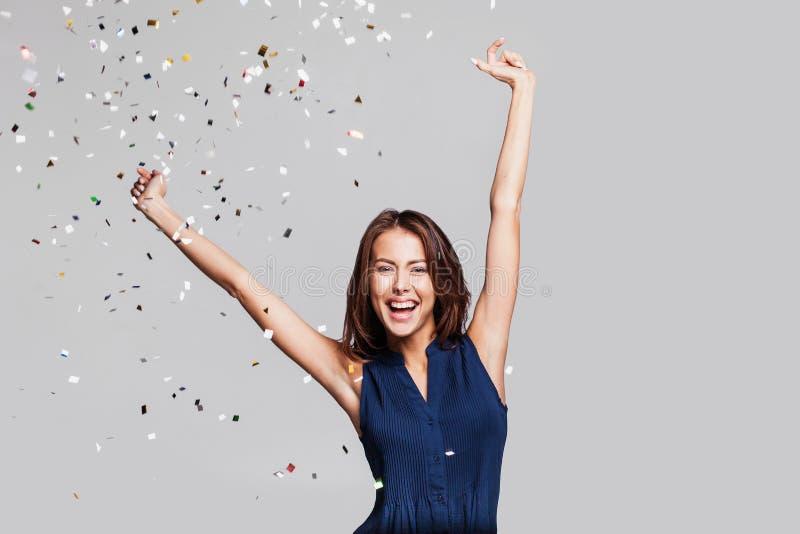 Schöne glückliche Frau an der Feierpartei mit den Konfettis, die überall auf sie fallen Des Geburtstages oder des Sylvesterabends lizenzfreie stockfotos