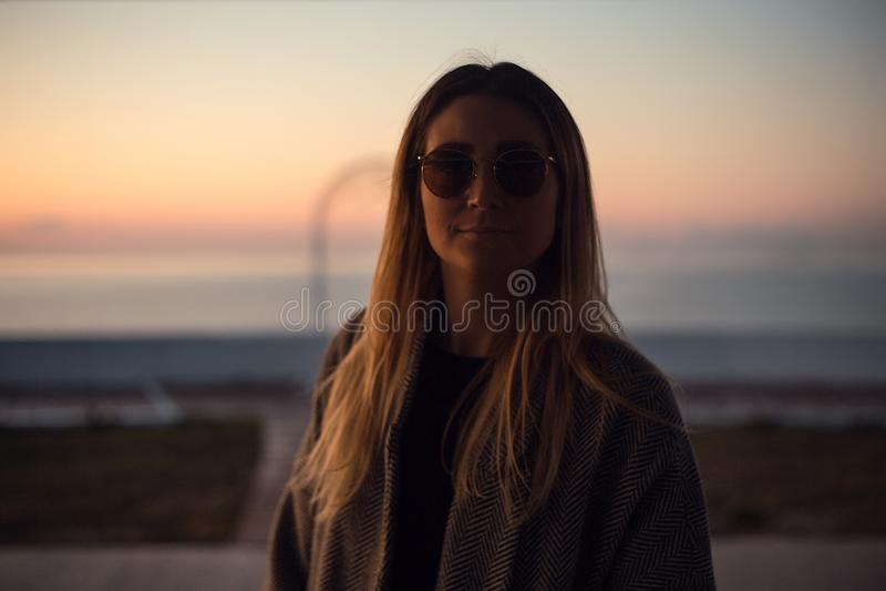Schöne glückliche Frau in der Sonnenbrille, die in dem Meer, Mädchen im grauen Mantel steht stockfotos