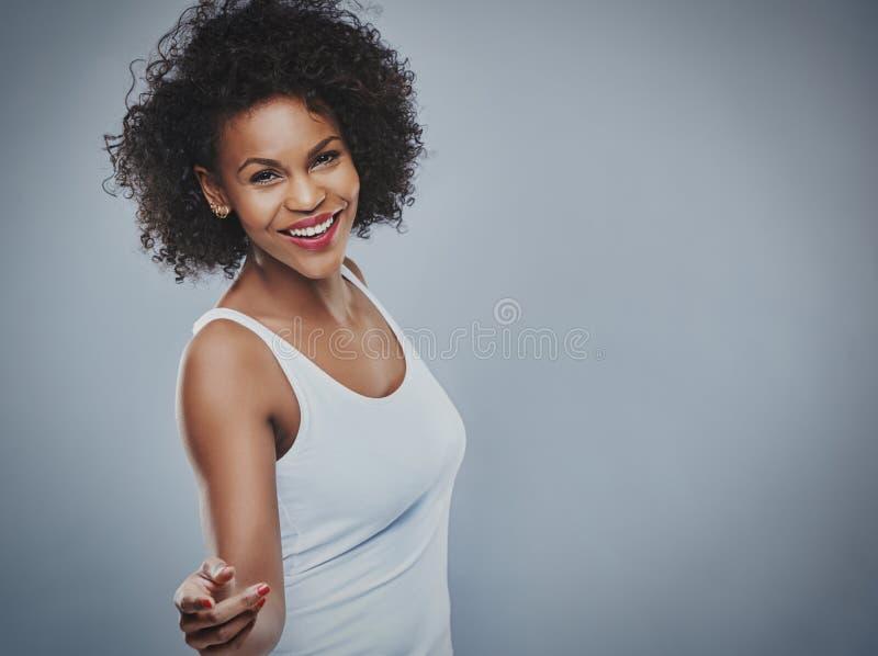 Schöne glückliche Frau, die über grauen Hintergrund tanzt stockfotos