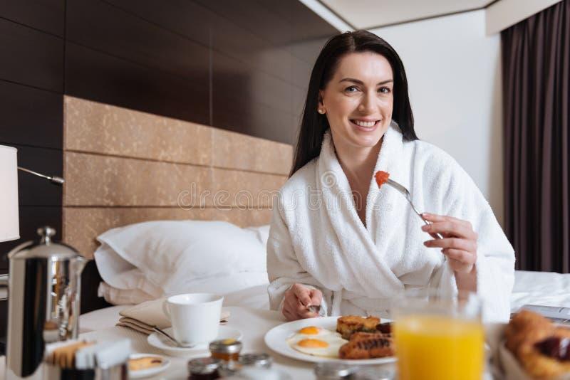 Schöne glückliche Frau, die ihr Frühstück isst stockfotos