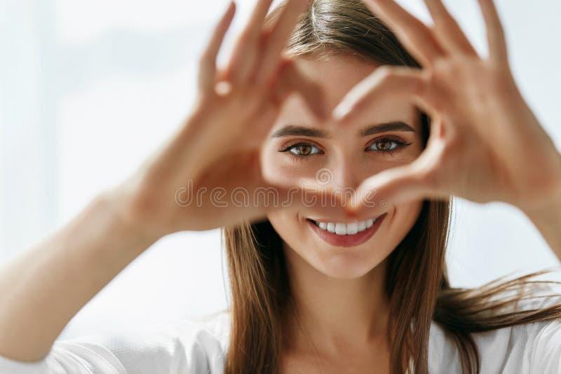 Schöne glückliche Frau, die Liebes-Zeichen nahe Augen zeigt stockbild
