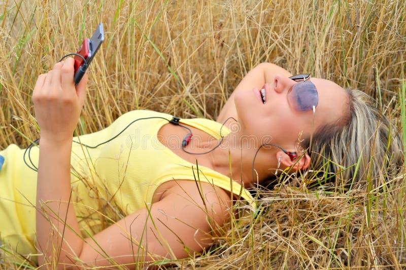 Schöne glückliche Frau, die Musik hört stockfotos