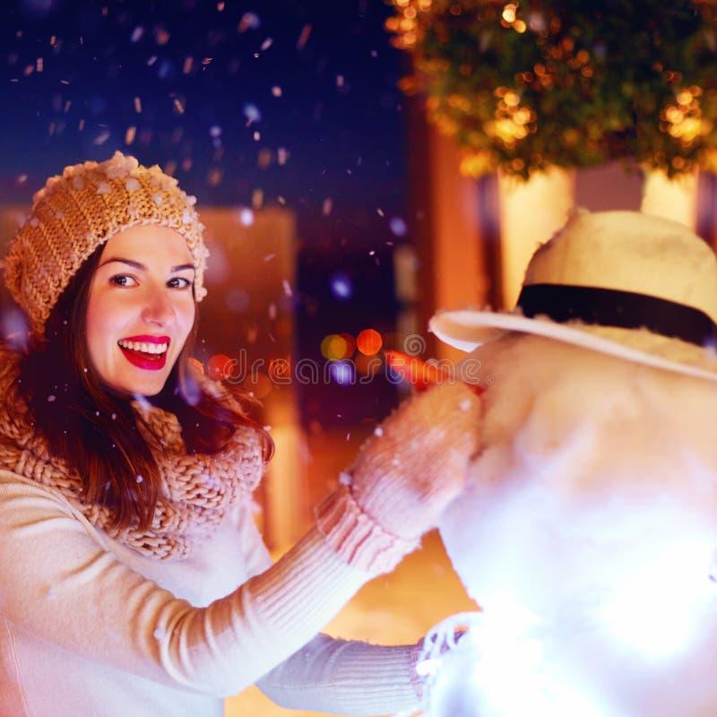 Schöne glückliche Frau, die Schneemann unter magischem Winterschnee macht lizenzfreies stockbild