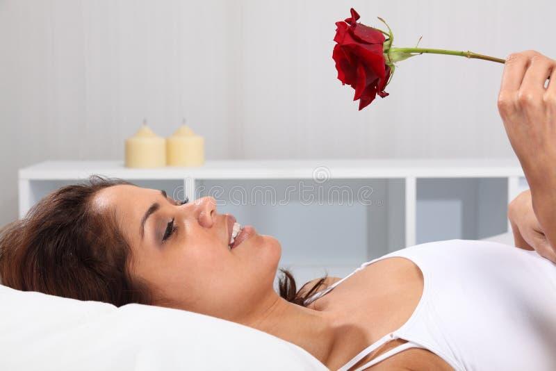Schöne glückliche Frau im Bett, das ein Rotes anhält, stieg lizenzfreies stockfoto