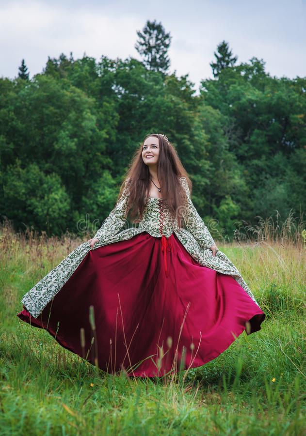 Sch?ne gl?ckliche Frau im mittelalterlichen Kleidertanzen im Freien stockfoto
