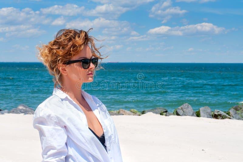 Schöne glückliche Frau im weißen Hemd, welches das Meer auf Strand betrachtet lizenzfreies stockfoto