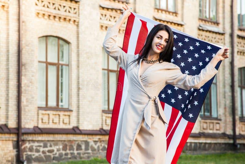 Schöne glückliche Frau mit amerikanischer Flagge Unabhängigkeitstag feiernd lizenzfreies stockfoto