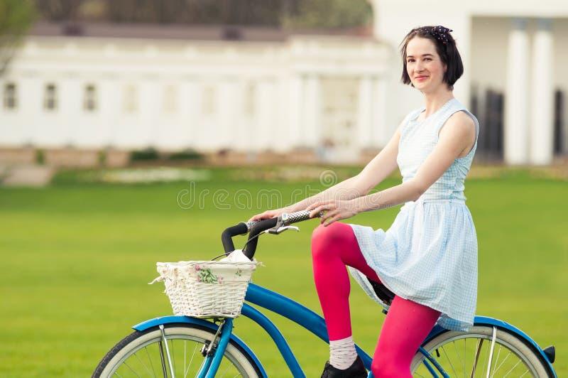 Schöne glückliche Frau mit Fahrrad im entspannenden Park lizenzfreies stockbild