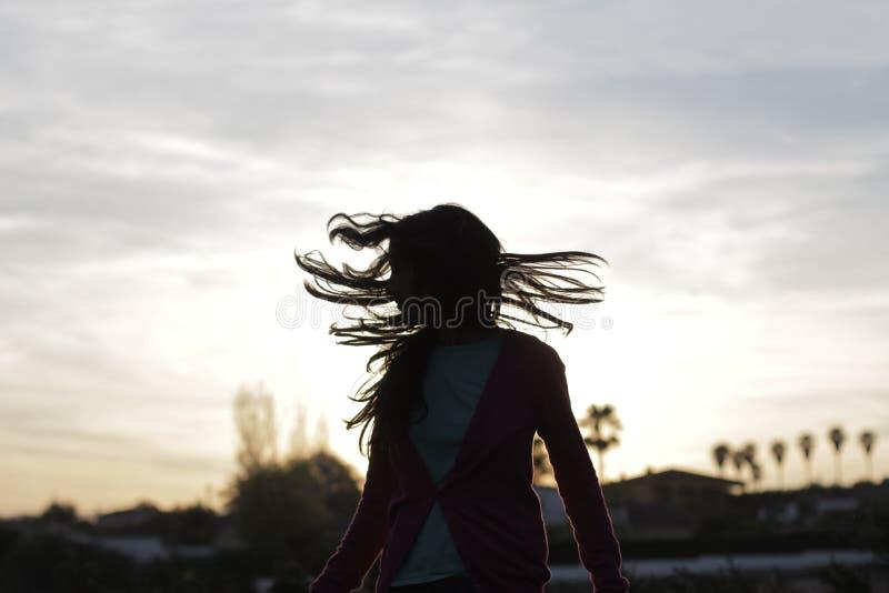 Schöne glückliche Frau mit Hintergrundbeleuchtung und den Haaren im Wind lizenzfreies stockbild