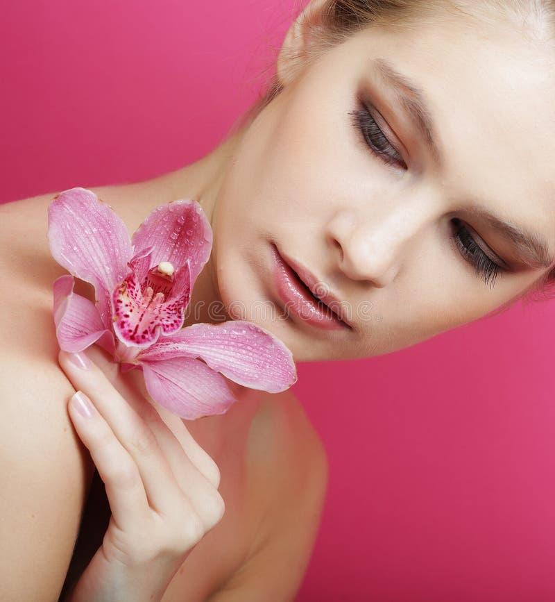 Schöne glückliche Frau mit Orchideenblume stockbild
