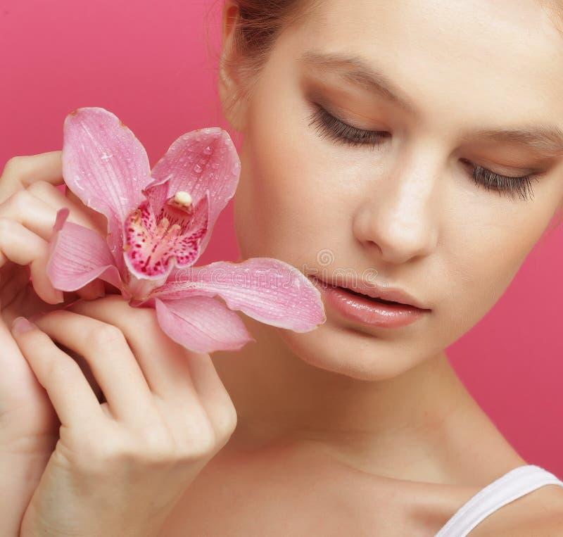 Schöne glückliche Frau mit Orchideenblume stockbilder