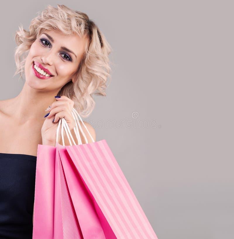 Schöne glückliche Frauenholdingeinkaufstasche Lächelndes vorbildliches Mädchen mit Make-up und nettem Lächeln stockfoto