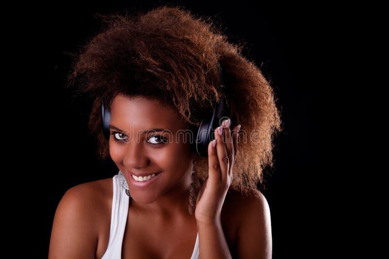 Schöne glückliche hörende Musik der schwarzen Frau lizenzfreies stockbild