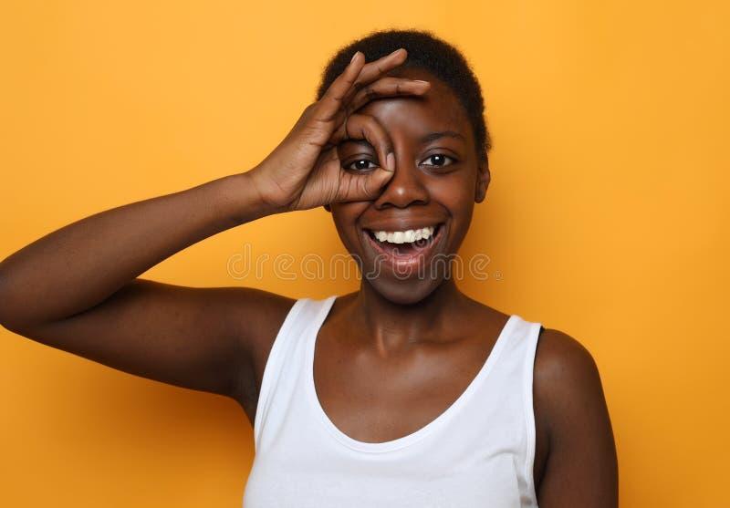 Schöne glückliche junge afrikanische Frau lokalisiert über gelbem Hintergrund stockbilder