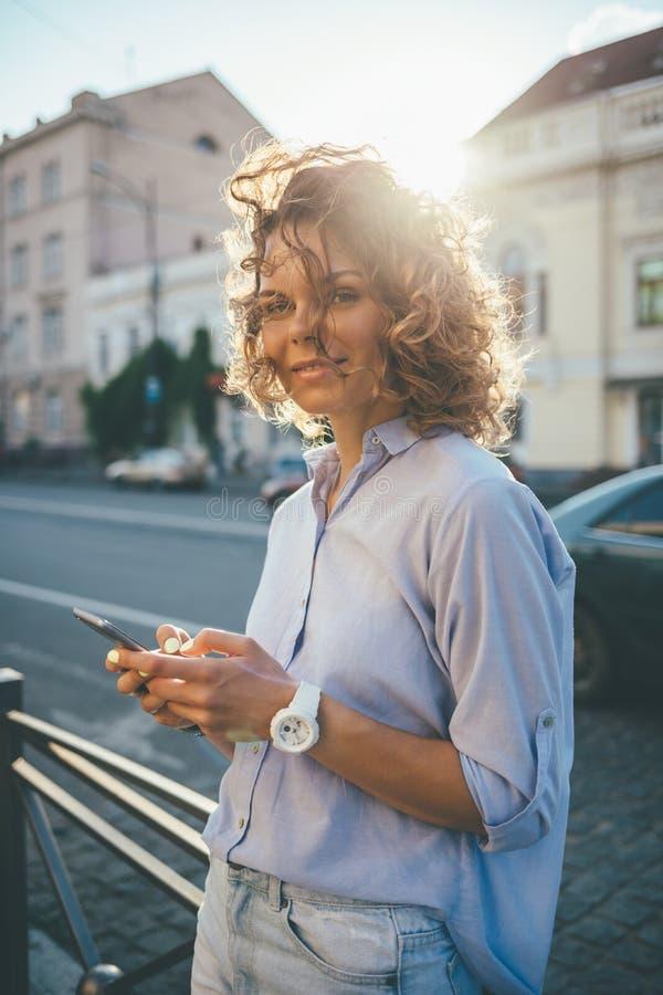 Schöne glückliche junge Frau, die blaues Hemd und Jeans trägt lizenzfreie stockfotografie