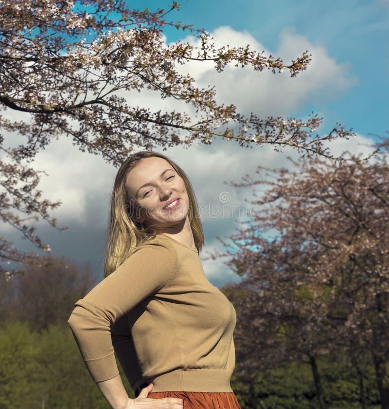 Schöne glückliche junge Frau, die Geruch in einem blühenden Frühling genießt lizenzfreies stockfoto