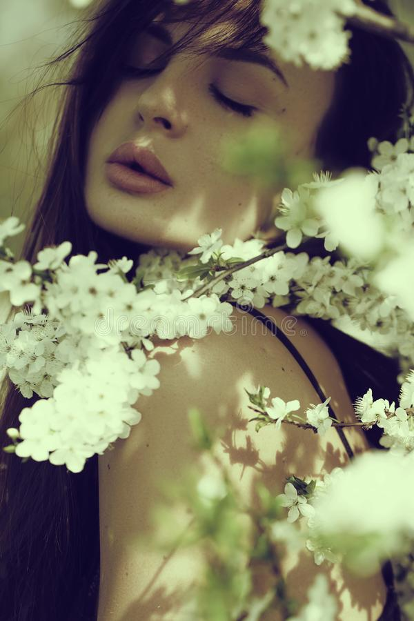 Schöne glückliche junge Frau, die Geruch in einem blühenden Frühlingsgarten genießt lizenzfreie stockbilder