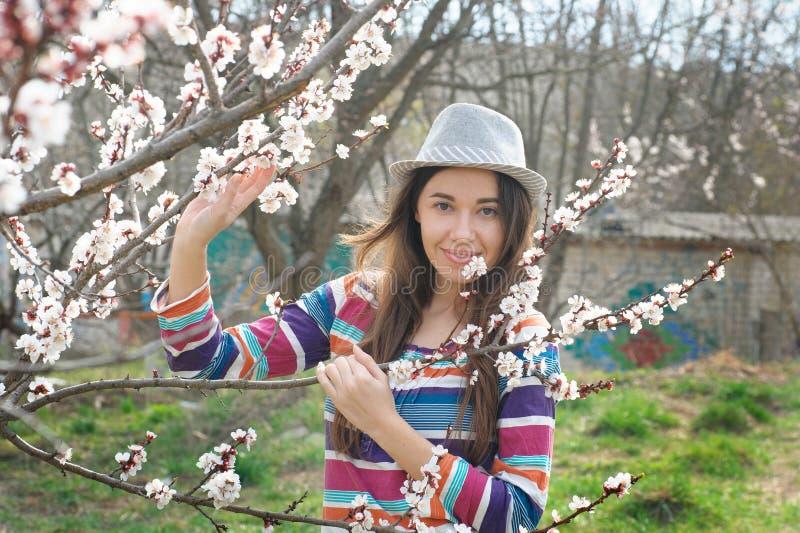 Schöne glückliche junge Frau, die Geruch in einem blühenden Frühlingsgarten genießt lizenzfreie stockfotografie