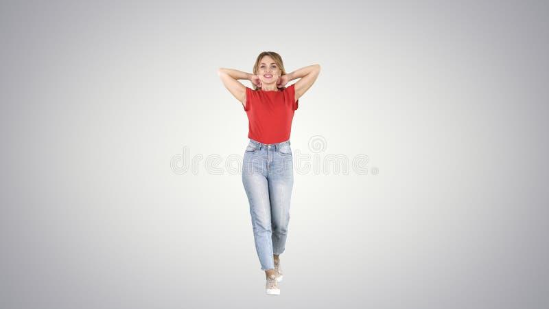 Schöne glückliche junge Frau, die morgens auf Steigungshintergrund geht und ausdehnt lizenzfreies stockbild