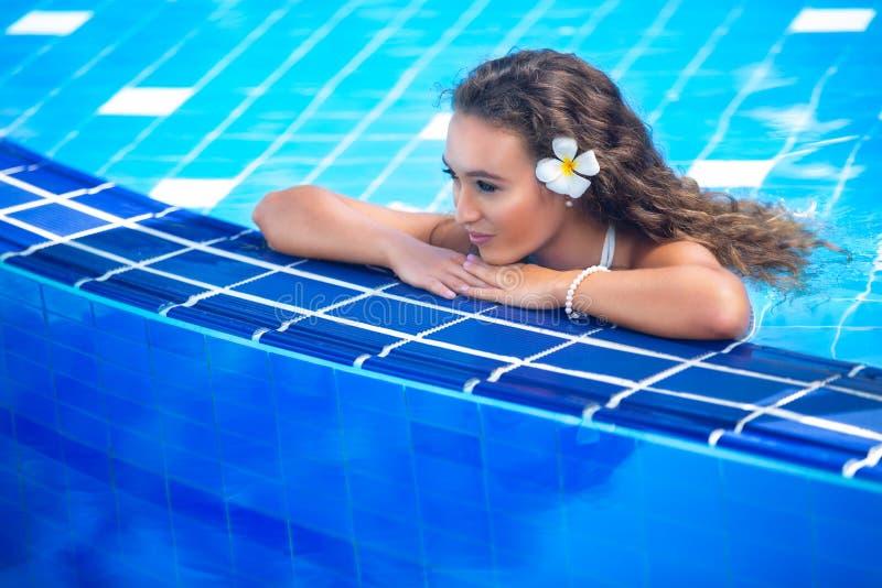 Schöne glückliche junge Frau im Swimmingpool stockfotografie
