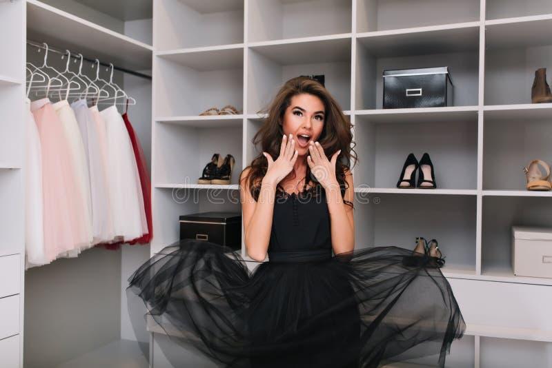 Schöne glückliche junge Frau mit dem langen braunen gelockten Haar angenehm überraschte, entsetzte so viel nette Kleidung im Luxu stockfoto