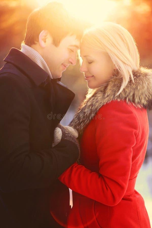 Schöne glückliche junge Paare des Winterporträts in der Liebe, sonniger warmer heller Sonnenuntergang lizenzfreie stockfotos