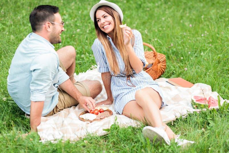 Schöne glückliche junge Paare, die zusammen ihre Zeit auf einem Picknick genießen stockfotografie