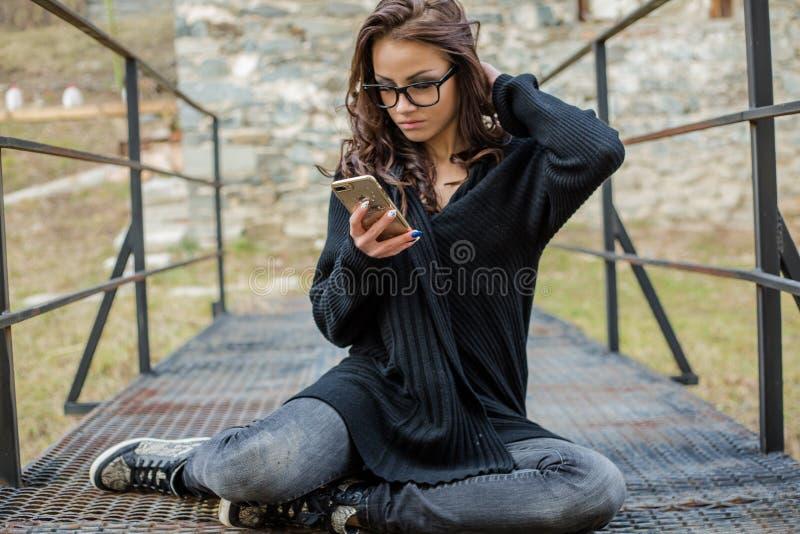 Schöne glückliche moderne Frau, die am Handy spricht stockfotografie
