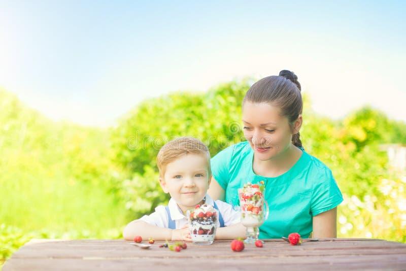 Schöne glückliche Mutter und ihr Kinderjunge, die überlagerten Nachtisch im grünen Garten am sonnigen Sommertag isst lizenzfreies stockbild