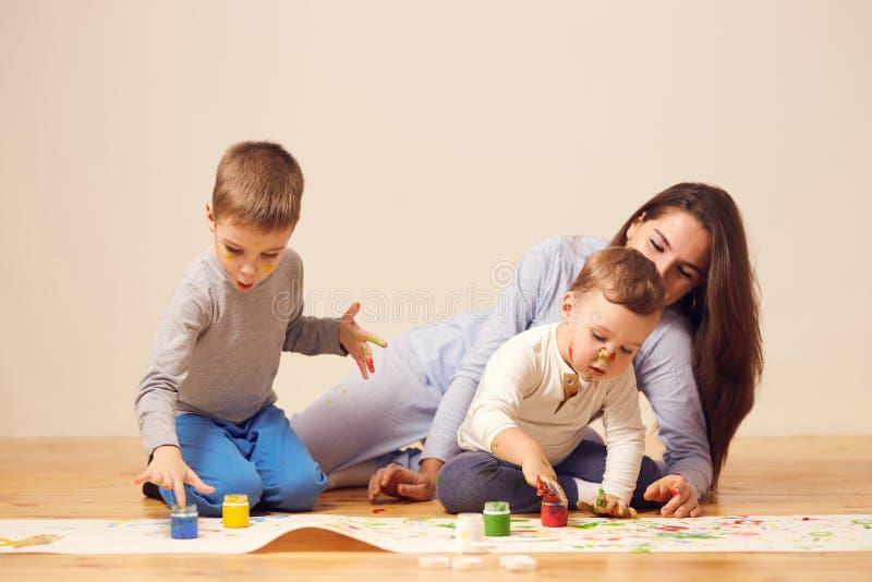 Schöne glückliche Mutter und ihre zwei kleinen die Söhne, die in der Hauptkleidung gekleidet werden, sitzen auf dem Bretterboden  lizenzfreies stockbild