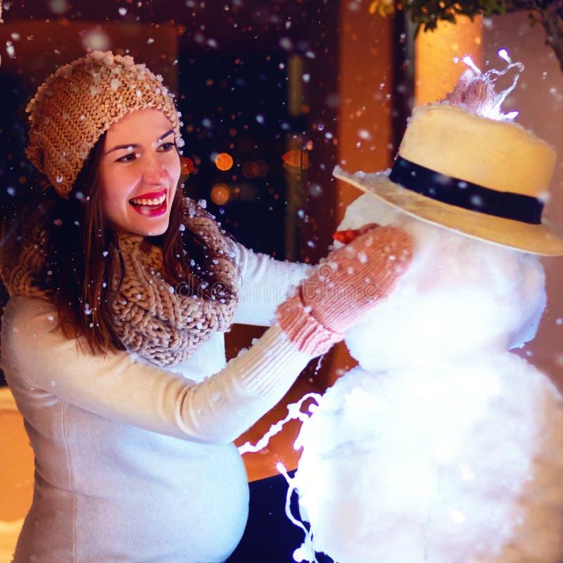 Schöne glückliche schwangere Frau, die Schneemann unter magischem Winterschnee macht stockbild